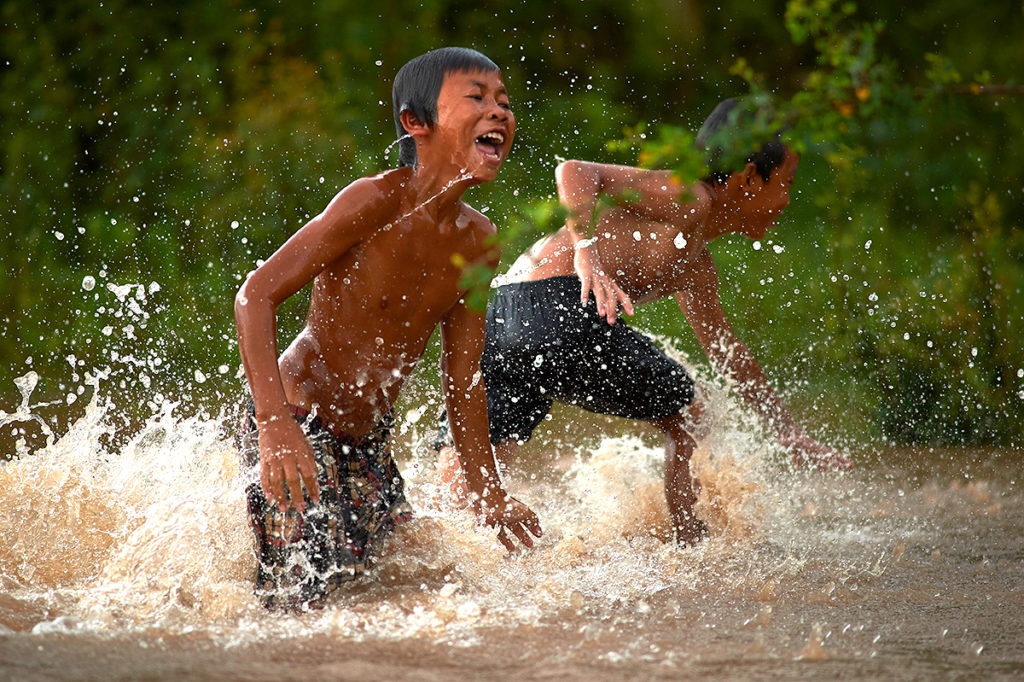 kids enjoy swimming in Mekong river